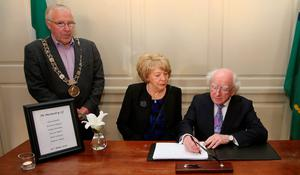 Lord Mayor Christy Burke (left) watches as President Michael D Higgins and his wife Sabina sign a book of condolence at Mansion House in Dublin for those killed in the Berkeley balcony collapse. PRESS ASSOCIATION Photo. Picture date: Thursday June 18, 2015. See PA story IRISH Balcony. Photo credit should read: Niall Carson/PA Wire