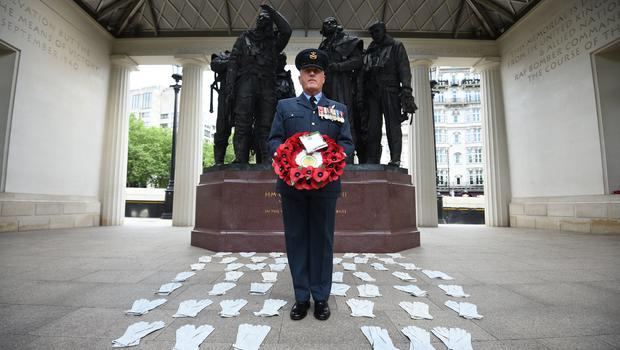 Flight Lieutenant Nigel Painter holds a wreath as he stands among 53 pairs of flying gloves at the Bomber Command Memorial in Green Park which represent the men who died in the Dambusters raids in 1943 (Kirsty O'Connor/PA)