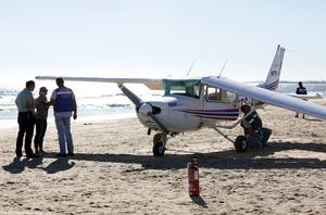 Portuguese coastguard officers check a small plane after an emergency landing at Sao Joao beach in Costa da Caparica, outside Lisbon
