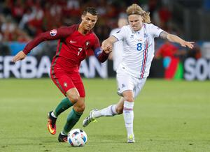 Portugal's Cristiano Ronaldo, left, is challenged by Iceland's Birkir Bjarnason during the Euro 2016 Group F soccer match between Portugal and Iceland at the Geoffroy Guichard stadium in Saint-Etienne, France, Tuesday, June 14, 2016. (AP Photo/Laurent Cipriani)