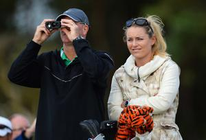 GULLANE, SCOTLAND - JULY 15:  Caddie Joe LaCava for Tiger Woods of the United States stands with skier Lindsey Vonn watches Tiger Woods of the United States ahead of the 142nd Open Championship at Muirfield on July 15, 2013 in Gullane, Scotland.  (Photo by Stuart Franklin/Getty Images)