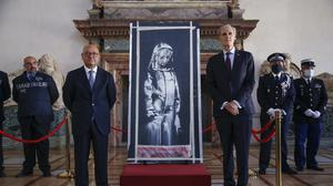 Franch ambassador to Italy, Christian Masset, right, and Italian prosecutor Michele Renzo pose next to the recovered artwork by Banksy (Domenico Stinellis/AP)