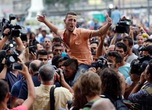 Migrants gather and shout slogans outside the railway station in Budapest, Hungary, Thursday, Sept. 3, 2015. Over 150,000 migrants have reached Hungary this year, most coming through the southern border with Serbia, and many apply for asylum but quickly try to leave for richer EU countries.(AP Photo/Frank Augstein)