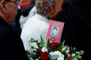 A man prepares to lay flowers bearing a photograph of one of the Hillsborough Disaster victims at the temporary Hillsborough memorial, ahead of a memorial service at Anfield in Liverpool, north west Engand on April 15, 2016, on the 27th anniversary of the Hillsborough Disaster. 96 Liverpool supporters died at the 1989 FA Cup semi-final between Liverpool and Nottingham Forest at the Hillsborough football ground in Sheffield, northern England. 2016 will be the final year a memorial service is held at Anfield. / AFP PHOTO / PAUL ELLISPAUL ELLIS/AFP/Getty Images