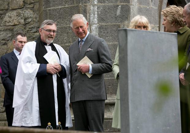 The Prince of Wales (centre) and the Very Rev. Arfon Williams at the grave of WB Yeats after attending a peace and reconciliation prayer service at St. Columba's Church in Drumcliffe on day two of a four day visit to Ireland. PRESS ASSOCIATION Photo. Picture date: Wednesday May 20, 2015. See PA story ROYAL Ireland. Photo credit should read: Colm Mahady/PA Wire