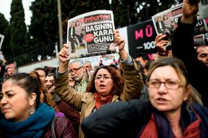 """People hold the Cumhuriyet Daily newspaper in front of the media headquarters, on November 27, 2015 in Istanbul, during a demonstration after the arrest of their Editor in Chief. A court in Istanbul charged two journalists from the opposition Cumhuriyet newspaper with spying after they alleged Turkey's secret services had sent arms to Islamist rebels in Syria, Turkish media reported. Editor-in-chief Can Dundar and Erdem Gul, the paper's Ankara bureau chief, are accused of spying and """"divulging state secrets"""". Both men were placed in pre-trial detention. AFP PHOTO/OZAN KOSEOZAN KOSE/AFP/Getty Images"""