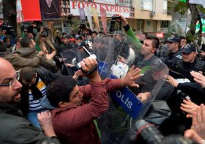 Riot police spray pepper gas toward journalists who were protesting against the jailing of opposition Cumhuriyet newspaper's editor-in-chief Can Dundar and Ankara representative Erdem Gul, in Ankara, Turkey, Friday, Nov. 27, 2015. The journalists accused the government of silencing critics and attempting to cover-up a scandal after Dundar and Gul were jailed on terror and espionage charges for their reports on alleged Turkish arms smuggling to Syria. Dundar and Gul were sent to a prison in Istanbul late on Thursday, accused of willingly aiding a terror organization and revealing state secrets, amid deepening concerns over media freedoms in the country that aspires to join the European Union. (AP Photo)