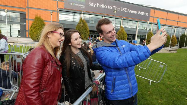 SSE Energiser Lee Waring along with 1D fans Sarah Emerson and Louise Stafford prepare to electrify the SSE Arena, Belfast this afternoon ahead of tonight's concert. Picture by Kelvin Boyes / Press Eye.