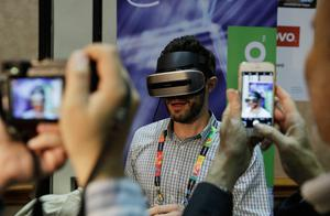 Chad Kresser demonstrates a prototype VR headset at the Lenovo booth during CES Unveiled before CES International, Tuesday, Jan. 3, 2017, in Las Vegas. The VR headset tracks head movements using cameras in the headset. (AP Photo/John Locher)