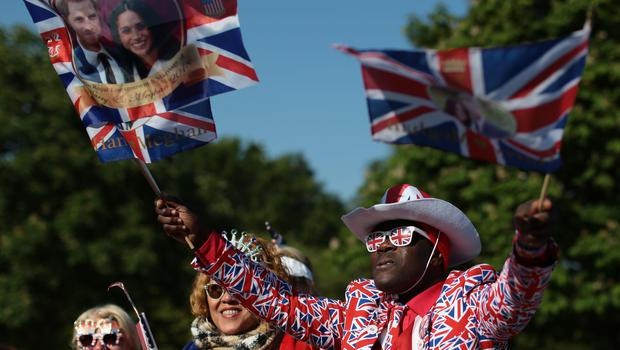 Flying the flag: a fan, flags in both hands, gets ready for the wedding (Aaron Chown/PA)