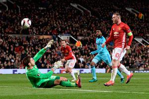 Manchester United's English striker Wayne Rooney (R) chips the ball over Feyenoord's Australian goalkeeper Brad Jones (L) to score the opening goal during the UEFA Europa League group A football match between Manchester United and Feyenoord at Old Trafford stadium in Manchester, north-west England, on November 24, 2016. / AFP PHOTO / Oli SCARFFOLI SCARFF/AFP/Getty Images