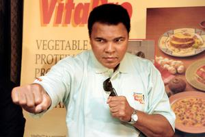 """This file photo taken on October 21, 1996 shows Boxing great Muhammad Ali throws a punch towards photographers during a press conference in Jakarta. Boxing icon Muhammad Ali died on Friday, June 3, a family spokesman said in a statement. """"After a 32-year battle with Parkinsons disease, Muhammad Ali has passed away at the age of 74,"""" spokesman Bob Gunnell said. / AFP PHOTO / JOHN MACDOUGALLJOHN MACDOUGALL/AFP/Getty Images"""