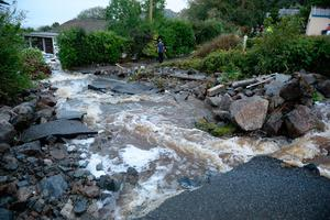 A driveway is lifted caused by water from flash flooding in the coastal village of Coverack in Cornwall. Ben Birchall/PA Wire