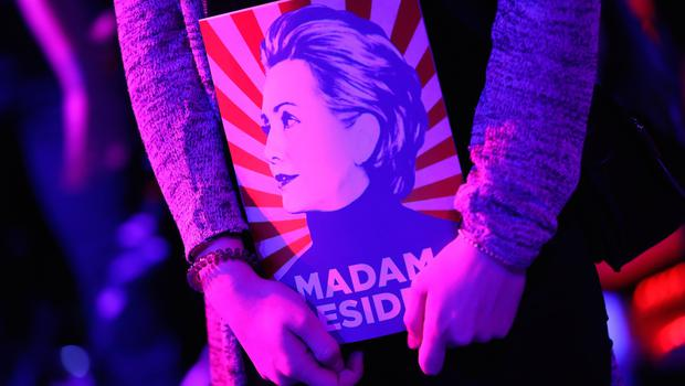 "BERLIN, GERMANY - NOVEMBER 08:  A guest clutches a magazine showing a stylized Hillary Clinton and that reads: ""Madam President"" at the Democrats Abroad U.S. elections party on November 8, 2016 in Berlin, Germany. Many Germans are watching the U.S. elections closely and a majority are hoping Hillary Clinton will defeat Donald Trump.  (Photo by Sean Gallup/Getty Images)"
