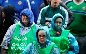 Northern Ireland fans show their support in the rain at the official fan zone at The Titanic Belfast, Belfast. PRESS ASSOCIATION Photo. Picture date Thursday June 16, 2016. See PA story SPORT Euro 2016 Belfast. Photo credit should read: Brian Lawless/PA Wire