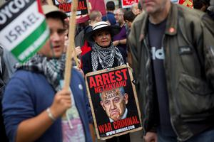 A pro-Palestinian demonstrator carrying a placard depicting Israeli Prime Minister Benjamin Netanyahu joins others during a protest outside the gates of Downing Street in London on September 9, 2015. Over 100 pro-Israeli demonstrators and hundreds of pro-Palestinian activists rallied in front of Downing Street in London ahead of a planned visit of Israeli Prime Minister Benjamin Netanyahu. Netanyahu visits Britain this week for talks with his counterpart David Cameron as the right-wing Israeli leader faces diplomatic pressure over West Bank settlements and stalled peace efforts. AFP PHOTO / JUSTIN TALLISJUSTIN TALLIS/AFP/Getty Images
