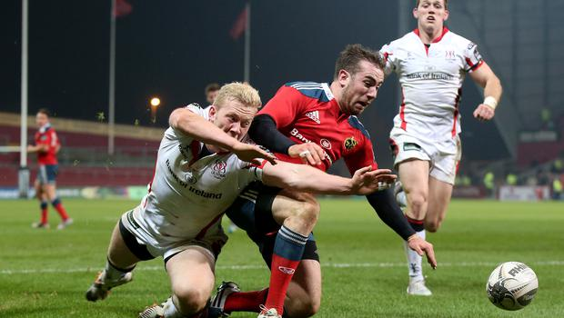 Dangerous time: Stuart Olding dives in to deny Munster's JJ Hanrahan a try
