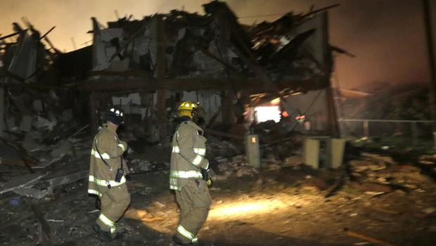 Firefighters walk next to a destroyed apartment complex near a fertilizer plant that exploded earlier in West, Texas, in this photo made early Thursday morning, April 18, 2013.  (AP Photo/LM Otero)