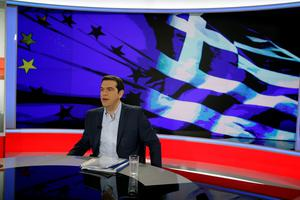 Greece's Prime Minister Alexis Tsipras prepares for a TV interview at the State Television (ERT) in Athens, Monday, June 29, 2015. Anxious pensioners swarmed closed bank branches Monday and long lines snaked at ATMs as Greeks endured the first day of serious controls on their daily economic lives ahead of a July 5 referendum that could determine whether the country has to ditch the euro currency and return to the drachma. (AP Photo/Thanassis Stavrakis)