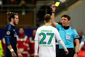 Italian referee Gianluca Rocchi gives a yellow card to Wolfsburg's midfielder Maximilian Arnold during the UEFA Champions League quarter-final, first-leg football match between VfL Wolfsburg and Real Madrid on April 6, 2016 in Wolfsburg, northern Germany.  / AFP PHOTO / John MACDOUGALLJOHN MACDOUGALL/AFP/Getty Images