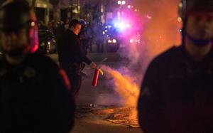 A police officer puts out a fire in the middle of a street during an anti-Trump protest in Oakland, California on November 9, 2016.  Thousands of protesters rallied across the United States expressing shock and anger over Donald Trump's election, vowing to oppose divisive views they say helped the Republican billionaire win the presidency. / AFP PHOTO / Josh EdelsonJOSH EDELSON/AFP/Getty Images