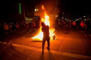 A man sprays lighter fluid on a burning trash fire at an intersection during an anti-Trump protest in Oakland, California on November 9, 2016.  Thousands of protesters rallied across the United States expressing shock and anger over Donald Trump's election, vowing to oppose divisive views they say helped the Republican billionaire win the presidency. / AFP PHOTO / Josh EdelsonJOSH EDELSON/AFP/Getty Images