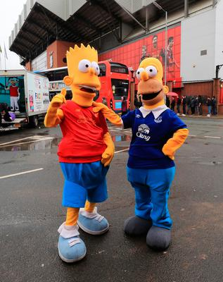 Fans dressed as Bart and Homer Simpson before the Premier League match at Anfield, Liverpool. PA
