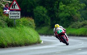 PACEMAKER, BELFAST, 5/6/2000:  48 year old Joey Dunlop pays no heed to the signs as he blasts into Ballaugh village on his  250cc Honda on his way to winning the Lightweight TT this afternoon at the Isle of Man  TT races. PICTURE BY STEPHEN DAVISON