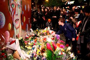 LONDON, ENGLAND - JANUARY 11:  A boy leaves flowers beneath a mural of David Bowie in Brixton on January 11, 2016 in London, England. British music and fashion icon David Bowie died earlier today at the age of 69 after a battle with cancer.  (Photo by Carl Court/Getty Images)