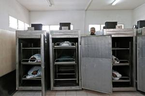A hospital worker opens the doors of the Rafah hospital morgue's cold storage, to show journalists the bodies of six Palestinians, killed in various Israeli airstrikes in the Rafah area, southern Gaza Strip, Wednesday, July 16, 2014. Israeli war planes and naval vessels intensified attacks across the Gaza Strip on Wednesday, targeting senior Hamas leaders and bombarding a coastal area, where four Palestinian boys were killed. The renewed violence came after Hamas formally rejected a cease-fire proposal that had been accepted by Israel to end the 9-day-old conflict that has left more than 200 Palestinians and one Israeli dead. (AP Photo/Lefteris Pitarakis)