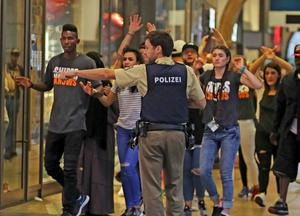 In this Friday, July 22, 2016 photo provided by Wael Ladki a police officer shows the way to people fleeing after a shooting in a shopping mall in Munich, southern Germany. (Wael Ladki via AP)