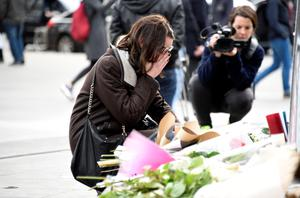 A young woman reacts in front of flowers and candles placed at the monument at the Place de la Republique in Paris on November 14, 2015, following a series of coordinated attacks in and around Paris late November 13, which left more than 120 people dead. AFP PHOTO / DOMINIQUE FAGETDOMINIQUE FAGET/AFP/Getty Images