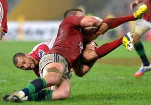 BRISBANE, AUSTRALIA - JUNE 08:  Quade Cooper of the Reds is tackled by Dan Lydiate of the Lions during the match between the Queensland Reds and the British & Irish Lions at Suncorp Stadium on June 8, 2013 in Brisbane, Australia.  (Photo by Bradley Kanaris/Getty Images)