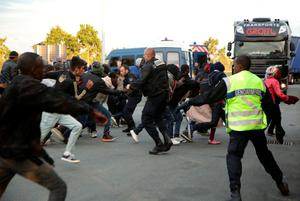 Migrants rush at a police cordon by a truck route along the perimeter fence of the Eurotunnel site at Coquelles in Calais, France. PRESS ASSOCIATION Photo. Picture date: Thursday July 30, 2015. Nine people have been killed attempting to cross the Channel in the last month, according to Eurotunnel, as migrants try to reach Britain. See PA story POLITICS Calais. Photo credit should read: Yui Mok/PA Wire