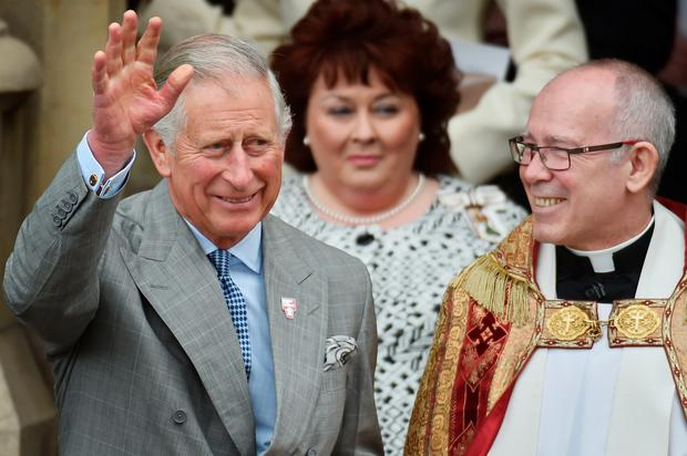 The Prince of Wales, waves as he walks out of St Patrick's Church, in Belfast, Northern Ireland, with Fr Michael Sheehan, as the Prince of Wales and the Duchess of Cornwall, attend a series of engagements in Northern Ireland following their two day visit in the Republic of Ireland. PRESS ASSOCIATION Photo. Picture date: Thursday May 21, 2015. The Prince of Wales has visited a Catholic church in Belfast that has been at the centre of a series of bitter marching disputes involving Protestant loyal orders and loyalist bands. St Patrick's Church has witnessed disorder and discord in recent years, with some parading loyalist bandsmen accused of provocative and sectarian behaviour while passing the place of worship. The visit of the prince and the Duchess of Cornwall will be seen as another symbolic gesture by a Royal family keen to contribute to reconciliation in Northern Ireland. See PA story ROYAL Ireland. Photo credit should read: Jeff J Mitchell/PA Wire