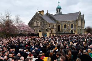 The funeral procession arrives with the coffin at St Columba's Church Long Tower for the funeral of former Northern Ireland Deputy First Minister Martin McGuinness in Derry, Northern Ireland on March 23, 2017. Former Irish Republican Army commander turned peace negotiator Martin McGuinness divided opinion both in life and in death but on Thursday his supporters gave him the funeral of an Irish chieftain. / AFP PHOTO / BEN STANSALLBEN STANSALL/AFP/Getty Images