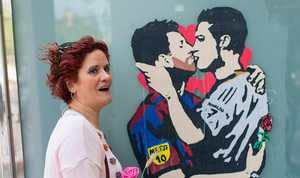 The beautiful game - football fans from around the world -  A woman holding a rose poses with the piece of street art titled Love is blind, depicting Barcelona's Lionel Messi and Real Madrid's Cristiano Ronaldo kissing by street artist Salva Tvboy, in Barcelona on April 23, 2017.