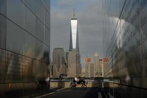 JERSEY CITY, NJ - SEPTEMBER 10: A man rides a bike as he pass by the 9/11 memorial in Liberty State Park with the new World Trade Center tower standing in the background on September 10, 2014 in Jersey City, New Jersey. Tomorrow the nation will mark the 13th anniversary of the September 11th attacks that left nearly 3,000 people dead. (Photo by Kena Betancur/Getty Images)