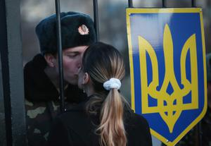 LUBIMOVKA, UKRAINE - MARCH 03:  Oleg, a Ukrainian soldier at the Belbek military base, kisses his girlfriend Svetlana through the gates of the base entrance on March 3, 2014 in Lubimovka, Ukraine. Tensions at the base, where between 100 and 200 Ukrainian soldiers are stationed, are high as a 4pm deadline reportedly given by Russian troops for the Ukrainians to surrender passed and locals feared the Russians might attack tonight. Heavily-armed soldiers who are not displaying identifying insignia but are widely believed to be Russians have blockaded several Ukrainian military bases across Crimea.   (Photo by Sean Gallup/Getty Images)