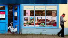 A man walks past an empty shop, which has been covered with artwork to make it look more appealing, in the village of Bushmills on the Causeway Coast August 19, 2013.