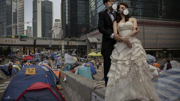 A young Hong Kong couple wear gas masks as they pose for a wedding photographer prior to their marriage next to the tents used by pro-deocracy demonstrators at the Admiralty protest site on November 14, 2014 in Hong Kong, Hong Kong.   (Photo by Kevin Frayer/Getty Images)