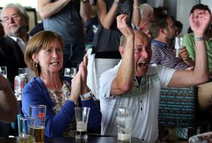 Fans watch Rory McIlroy win The Open on tv screens at Holywood Golf Course, County Down.