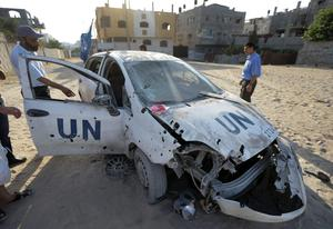 Palestinians gather around a United Nations aid agency car that was damaged by shrapnel from an Israeli strike, in the Jebaliya refugee camp, northern Gaza Strip, Tuesday, July 29, 2014. (AP Photo/Lefteris Pitarakis)