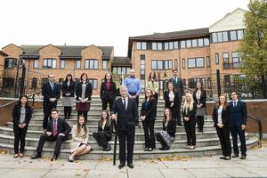 Nigel Harra is joined by the firm's new recruits, including apprentice Adam McDonald (right of the centre rail)