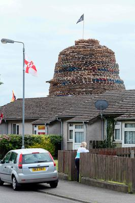 A bonfire towers over the housing in the Ballymacash area of Lisburn. [Photo: Paul Faith/AFP/Getty Images]