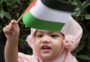 A Thai-Muslim girl waves a small Palestinian flag as her parents attend a rally outside the Israeli embassy in Bangkok, Thailand Tuesday, July 15, 2014. Several hundreds of activists took part in the rally to show solidarity for Palestine against Israel's attacks on Gaza. (AP Photo/Apichart Weerawong)