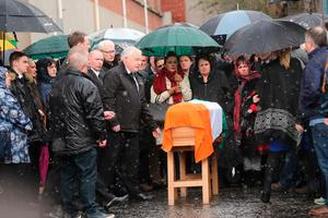 The coffin of Northern Ireland's former deputy first minister and ex-IRA commander Martin McGuinness is placed on a stand as it is carried to his home in Londonderry after he died aged 66.  Niall Carson/PA Wire