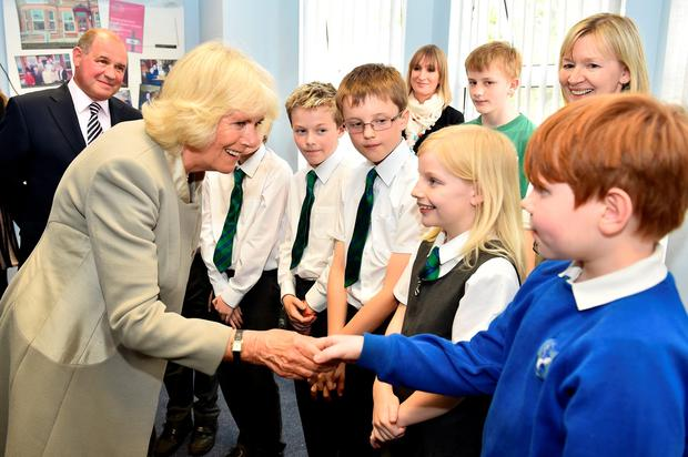 The Duchess of Cornwall meets school children as she visits Ballyhackamore Credit Union in Belfast, Northern Ireland, as the Prince of Wales and Camilla, attend a series of engagements in Northern Ireland following their two day visit in the Republic of Ireland. PRESS ASSOCIATION Photo. Picture date: Thursday May 21, 2015. See PA story ROYAL Ireland. Photo credit should read: Jeff J Mitchell/PA Wire