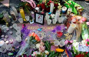 """Candles, flowers and other momentos are placed on the Hollywood Star of the late British musician David Bowie in Hollywood, California, on January 11, 2016. Bowie died at the age of 69 after a secret battle with cancer, prompting a cascade of tributes for one of the most influential and innovative artists of his time. A notoriously private person, Bowie's death was a shock with his death coming just two days after he released his 25th studio album """"Blackstar"""", on his 69th birthday on January 8. """"David Bowie died peacefully today (Sunday) surrounded by his family after a courageous 18-month battle with cancer,"""" said a statement posted January 11on his official social media accounts.  AFP PHOTO/FREDERIC J. BROWNFREDERIC J. BROWN/AFP/Getty Images"""
