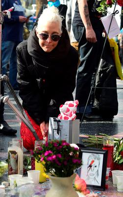 """A woman pays her respects at the Hollywood Star of the late British musician David Bowie in Hollywood, California, on January 11, 2016. Bowie died at the age of 69 after a secret battle with cancer, prompting a cascade of tributes for one of the most influential and innovative artists of his time. A notoriously private person, Bowie's death was a shock with his death coming just two days after he released his 25th studio album """"Blackstar"""", on his 69th birthday on January 8. """"David Bowie died peacefully today (Sunday) surrounded by his family after a courageous 18-month battle with cancer,"""" said a statement posted January 11on his official social media accounts.  AFP PHOTO/FREDERIC J. BROWNFREDERIC J. BROWN/AFP/Getty Images"""